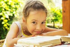 相当读一本旧书的卷曲学校女孩外面 免版税库存照片