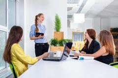 相当给在会议的一个介绍或遇见设置的年轻女商人 愉快人和配合的概念- 免版税库存照片