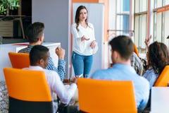 相当给在会议的一个介绍或遇见设置的年轻女商人 免版税库存照片