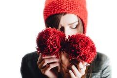 相当戴在白色背景的少妇一个手工编织的红色帽子 查出 美丽的女孩与耳朵挡水板 免版税库存照片