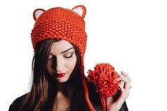 相当戴在白色背景的少妇一个手工编织的红色帽子 查出 美丽的女孩与耳朵挡水板 库存图片