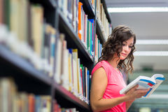 相当年轻女学生在寻找书的图书馆里 免版税库存照片