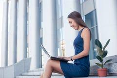 相当年轻女实业家使用一台膝上型计算机为 库存图片