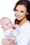 相当年轻妈妈运载的微笑的逗人喜爱的婴孩 免版税库存照片