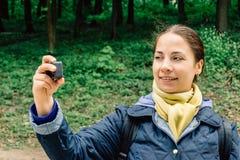 相当年轻旅行家博客作者女孩在行动照相机射击或记录自己 免版税库存图片