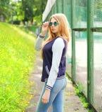 相当戴粗呢夹克和太阳镜的年轻白肤金发的女孩 库存照片