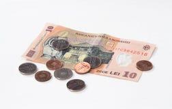 相当10罗马尼亚列伊价值的一张钞票与相当10和5罗马尼亚语在白色背景隔绝的巴尼价值的几枚硬币 免版税库存图片