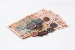 相当10罗马尼亚列伊价值的三张钞票与相当10和5罗马尼亚语在白色背景隔绝的巴尼价值的几枚硬币 库存图片