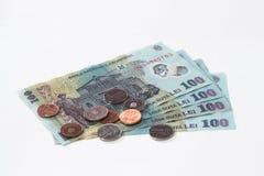 相当100罗马尼亚列伊价值的四张钞票与相当10和5罗马尼亚语在白色背景隔绝的巴尼价值的几枚硬币 免版税库存照片
