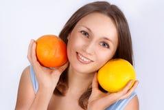 相当年轻美丽的妇女画象用两个葡萄柚 库存照片