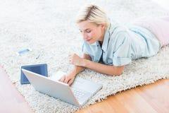 相当说谎在地板上和使用她的膝上型计算机的白肤金发的妇女 免版税图库摄影