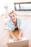 相当说谎在地板上和使用她的膝上型计算机的白肤金发的妇女 图库摄影