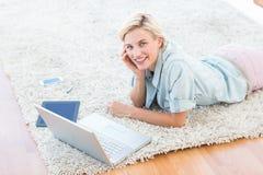 相当说谎在地板上和使用她的膝上型计算机的白肤金发的妇女 库存照片