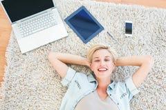 相当说谎在地板上和微笑对照相机的白肤金发的妇女 免版税库存照片