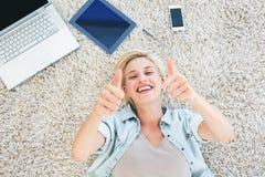 相当说谎在地板上和微笑对照相机赞许的白肤金发的妇女 库存照片