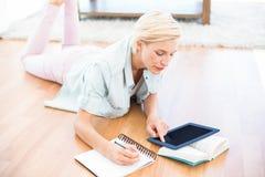 相当说谎在地板上和采取笔记的白肤金发的妇女,当使用她的片剂时 免版税图库摄影