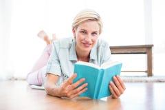 相当说谎在地板上和读书的白肤金发的妇女 库存照片