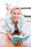 相当说谎在地板上和读书的白肤金发的妇女 库存图片