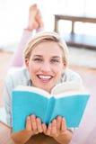相当说谎在地板上和读书的白肤金发的妇女 图库摄影