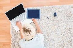 相当说谎在地板上的白肤金发的妇女,当使用她的膝上型计算机和片剂时 免版税库存图片