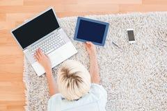 相当说谎在地板上的白肤金发的妇女,当使用她的膝上型计算机和片剂时 库存照片