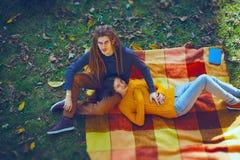 相当说谎在格子花呢披肩,秋天的年轻夫妇,拥抱时间, 免版税图库摄影