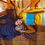 相当说谎在格子花呢披肩,秋天的年轻夫妇,拥抱时间, 免版税库存图片
