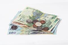 相当100, 10和1罗马尼亚人列伊价值的几张钞票与相当10和5罗马尼亚语在白色背景隔绝的巴尼价值的几枚硬币 免版税库存照片