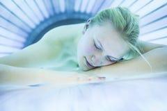 相当年轻womanin一个现代日光浴室 免版税图库摄影