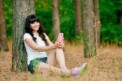 相当holdiing手机和微笑的少妇 免版税库存照片
