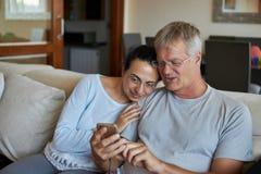 看一个手机的中年夫妇 免版税库存图片