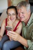 看一个手机的中年夫妇 免版税图库摄影