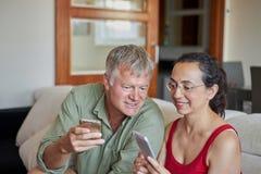 看一个手机的中年夫妇 免版税库存照片