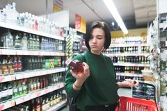 看一个瓶酒的女孩的画象在她的手上在购物期间 购物酒精在超级市场 免版税库存照片