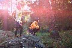 看一个看法的骑自行车的人夫妇在森林里 库存照片