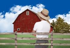 看一个红色谷仓的农夫 库存照片