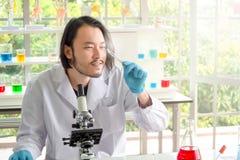 看一个药片在实验室,在医疗实验的年轻人测试的医学的亚裔科学家或化学家 r 免版税图库摄影