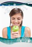 看一个绿色苹果的微笑的少年的综合图象安置在她的横渡的手 图库摄影