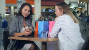 看一件新的礼服的愉快的亚裔妇女,她白肤金发的朋友在商城拍照片她 免版税库存照片