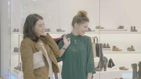 看一双鞋的少年姐妹在窗口商店谈论和笑关于他们奇怪的设计的购物中心- 影视素材