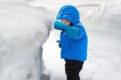 看一家深雪银行的男孩 免版税库存照片