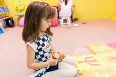 看一张五颜六色的难题戏剧席子的逗人喜爱的幼儿园女孩 库存图片