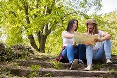 看一张地图的两个美丽的朋友在森林里 免版税库存照片