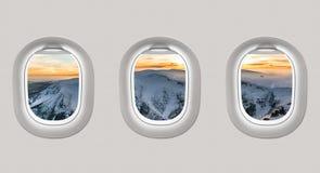 看一架飞机的窗口对冬天山的 库存图片