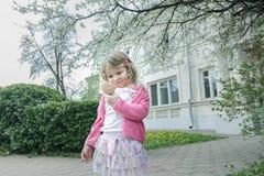 看一点口袋镜子的学龄前儿童女孩室外春天画象在春天围场 库存图片