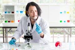 看一种片剂在实验室,在医疗实验的年轻人测试的医学的亚裔科学家或化学家 r 库存图片