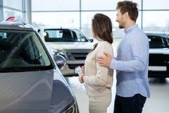看一辆新的汽车的美好的年轻夫妇经销权陈列室 免版税库存图片