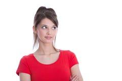 看一件红色的衬衣的俏丽的妇女斜向一边。 免版税图库摄影