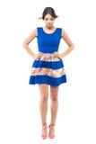 看下来与有风飞行头发的蓝色夏天礼服的逗人喜爱的妇女 免版税库存图片