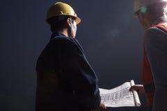 看下来图纸的安全帽的两位年轻男性工程师黄昏,背面图 免版税库存图片